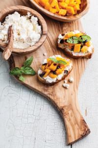 Bruschetta with chopped mango, basil and goat cheese on fresh ba